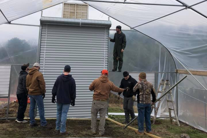 Picture of a group of men helping assemble a high tunnel greenhouse