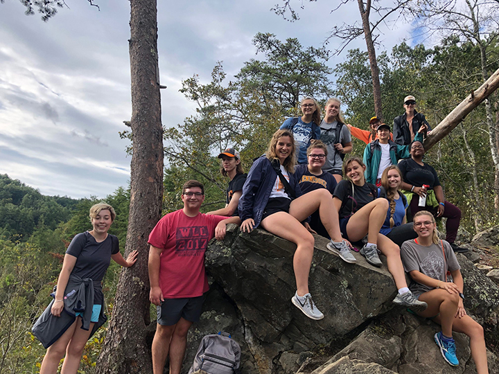 A group of students pose on a rock along a mountain trail