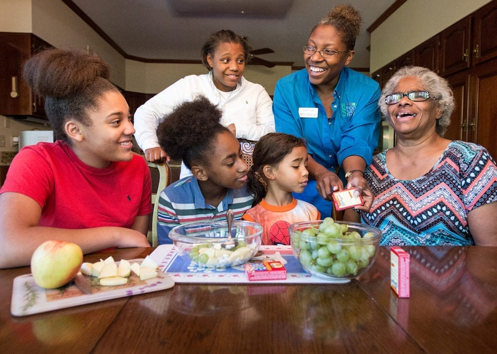 An Extension agent shows a family how to prepare healthy snacks