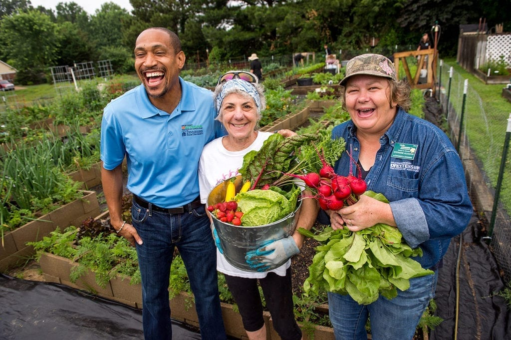 A man and two women stand in front of green rows of garden vegetables, one woman holding a bucket full of produce