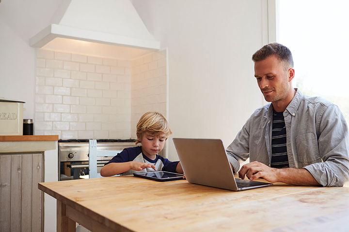 A father works on his laptop at a table while his son sits beside him using a tablet
