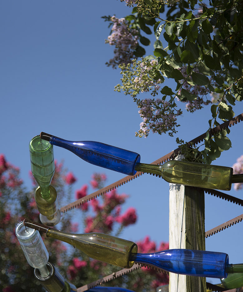 Glass bottle art is displayed against a hazy blue sky