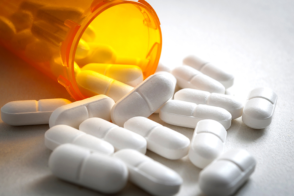 A prescription bottle is open on its side, with white pills spilling out