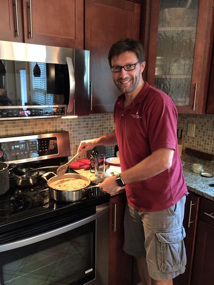 Luca Giori stands beside a stove with a pot of risotto and a wooden spoon